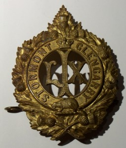 "Helmet plate, 59th Regiment, ca 1904. Made of gilding metal it shows the roman numeral LIX within a circle, surmounted by a Royal Crown with a beaver below, and the words ""Stormont"" and ""Glengarry"" on the circle, with the whole surrounded by a wreath of thistle leaves and flowers."